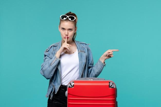 Mulher jovem se preparando para uma viagem e pedindo para ficar quieta no espaço azul
