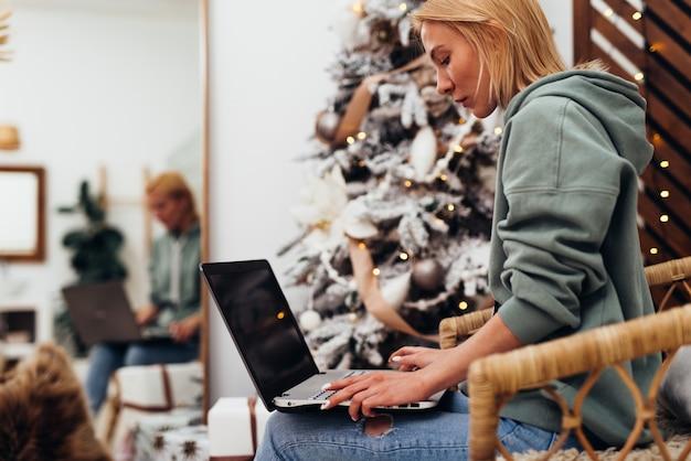 Mulher jovem se senta em uma poltrona com o computador portátil.