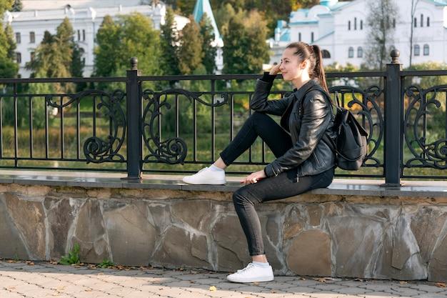 Mulher jovem se senta perto da cerca. caminhe ao longo do aterro. templo ao fundo.