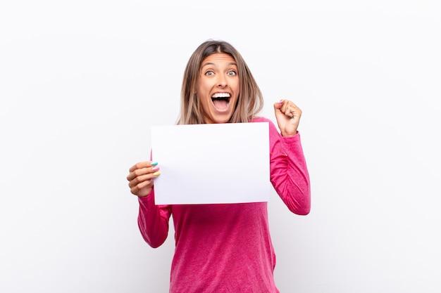 Mulher jovem se sentindo chocada, animada e feliz, rindo e comemorando o sucesso, dizendo uau! segurando um cartaz