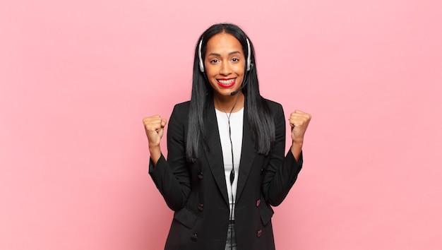Mulher jovem se sentindo chocada, animada e feliz, rindo e comemorando o sucesso, dizendo uau!