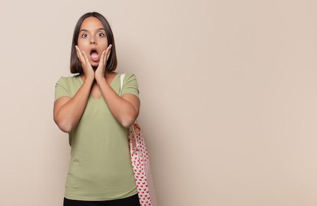 Mulher jovem se sentindo chocada e assustada, parecendo apavorada com a boca aberta e as mãos nas bochechas