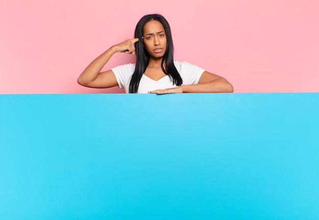 Mulher jovem se sentindo confusa e perplexa, mostrando que você é louco, louco ou maluco