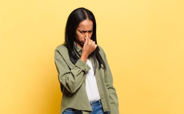 Mulher jovem se sentindo enojada, segurando o nariz para evitar cheirar um fedor desagradável e desagradável