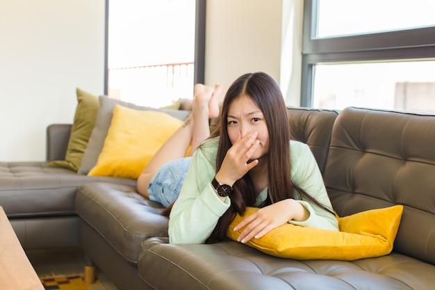 Mulher jovem se sentindo enojada, segurando o nariz para evitar cheirar um fedor repugnante e desagradável