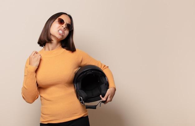 Mulher jovem se sentindo estressada, ansiosa, cansada e frustrada, puxando o pescoço da camisa