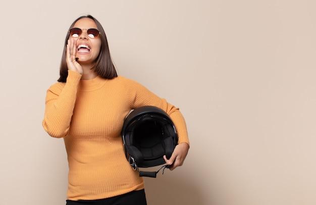 Mulher jovem se sentindo feliz, animada e positiva, dando um grande grito com as mãos perto da boca, gritando