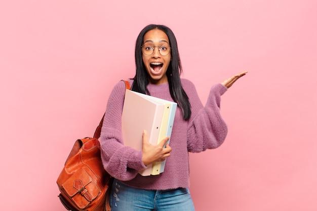 Mulher jovem se sentindo feliz, animada, surpresa ou chocada, sorrindo e espantada com algo inacreditável