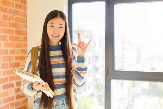 Mulher jovem se sentindo feliz, divertida, confiante, positiva e rebelde, fazendo sinal de rock ou heavy metal com a mão