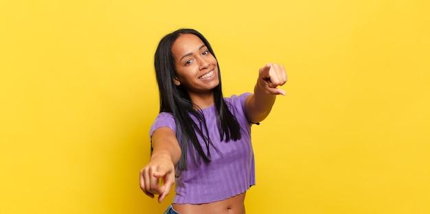 Mulher jovem se sentindo feliz e confiante, apontando para a câmera com as duas mãos e rindo, escolhendo você