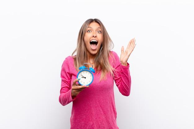 Mulher jovem se sentindo feliz, excitada, surpresa ou chocada, sorrindo e atônita com algo inacreditável segurando um despertador.
