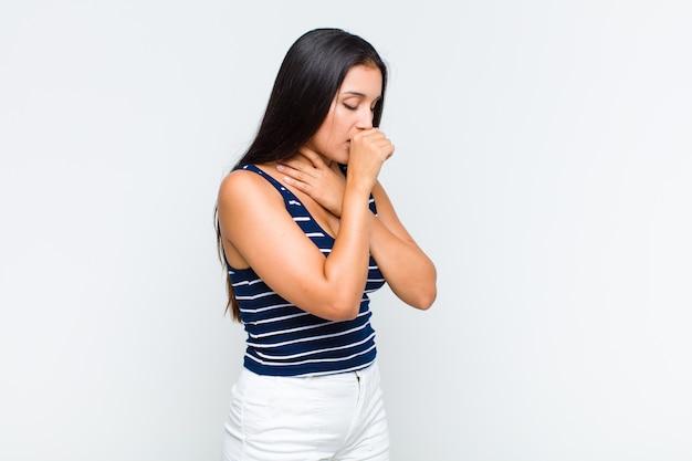 Mulher jovem se sentindo mal, com dor de garganta e sintomas de gripe, tosse com a boca coberta