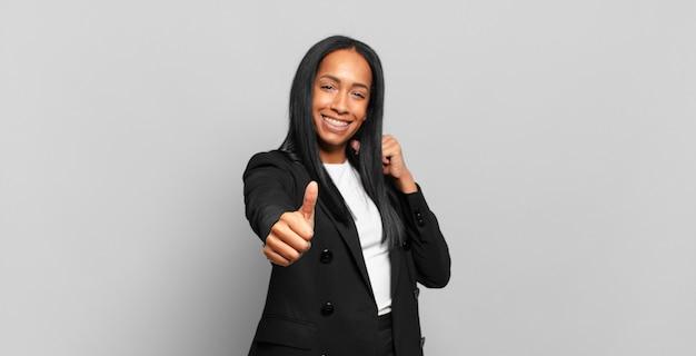 Mulher jovem se sentindo orgulhosa, despreocupada, confiante e feliz, sorrindo positivamente com o polegar para cima