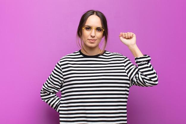 Mulher jovem se sentindo séria, forte e rebelde, levantando o punho, protestando ou lutando pela revolução na parede roxa