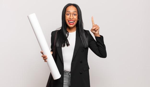 Mulher jovem se sentindo um gênio feliz e animado depois de realizar uma ideia, levantando o dedo alegremente, eureka!
