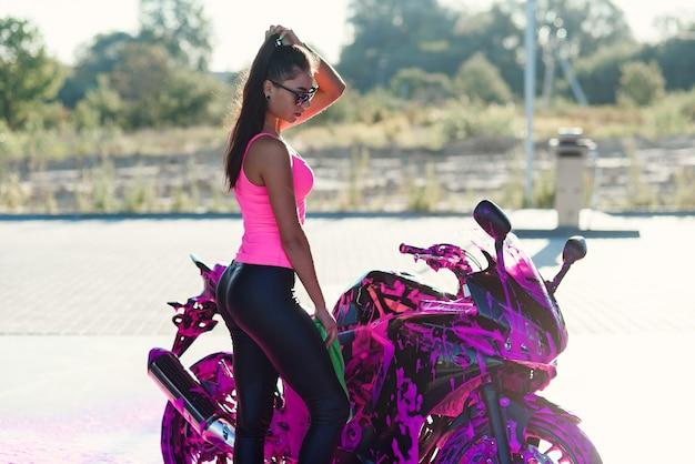 Mulher jovem sedutora em uma camiseta rosa posa perto de uma motocicleta esportiva no lava-rápido