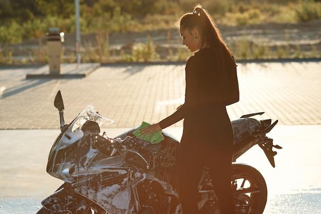 Mulher jovem sedutora lavando motocicleta esporte elegante e enxugando-a de espuma roxa. cuidando do veículo.