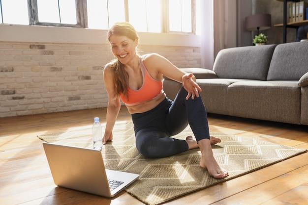 Mulher jovem segue com um laptop, exercícios de ginásio.