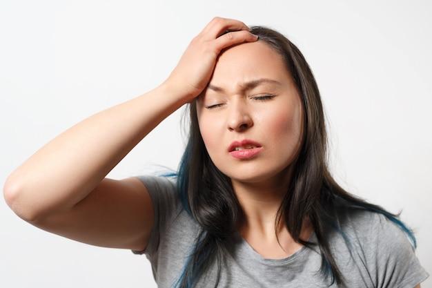 Mulher jovem segura a cabeça com a mão por causa de uma dor de cabeça em branco