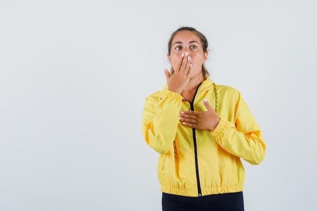 Mulher jovem segurando a boca com a mão na capa de chuva amarela e parecendo assustada