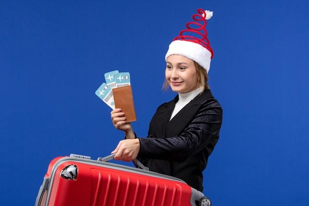 Mulher jovem segurando a bolsa de frente e ingressos para as férias de férias de avião de parede azul