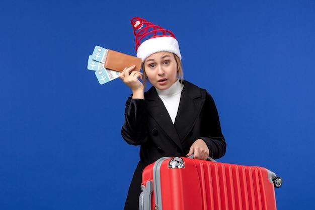 Mulher jovem segurando a bolsa de frente e passagens de avião em viagem de férias de avião de parede azul