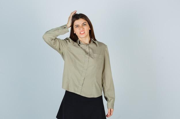 Mulher jovem segurando a cabeça com a camisa, saia e parecendo esquecida
