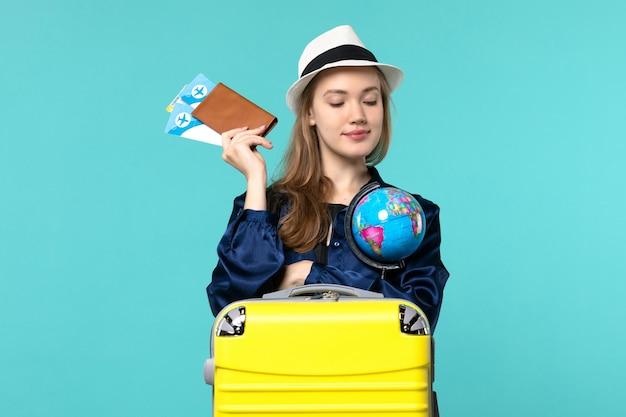 Mulher jovem segurando a carteira com ingressos na mesa azul avião viagem mulher viagem mar férias