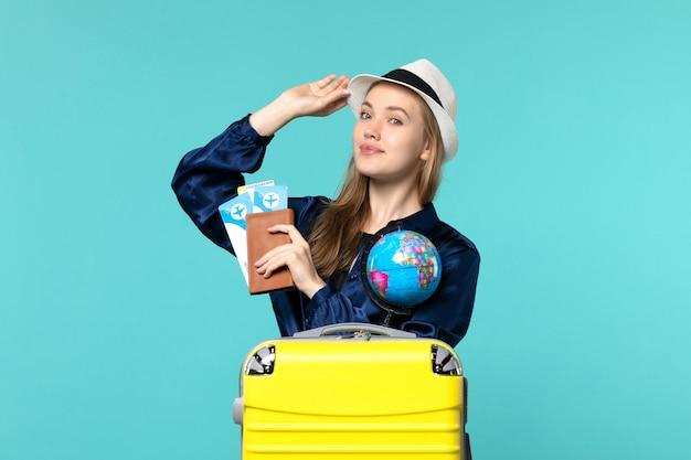 Mulher jovem segurando a carteira com ingressos no fundo azul avião viagem mulher viagem mar férias