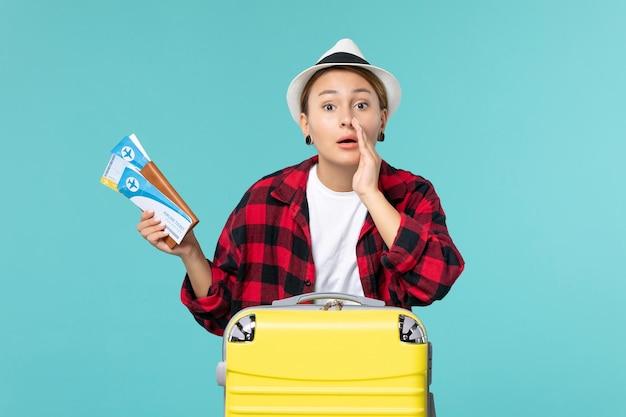 Mulher jovem segurando a carteira de frente com ingressos no espaço azul claro