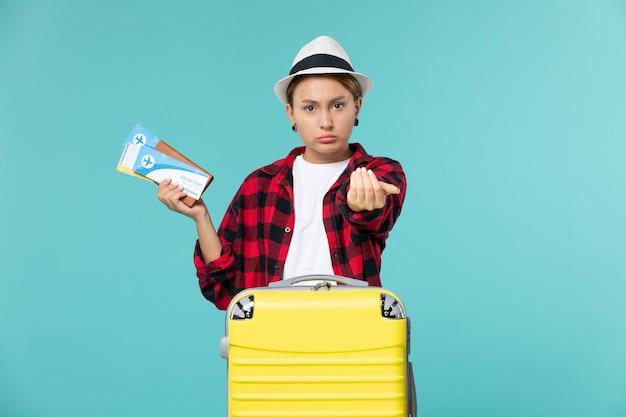 Mulher jovem segurando a carteira de frente com ingressos no espaço azul