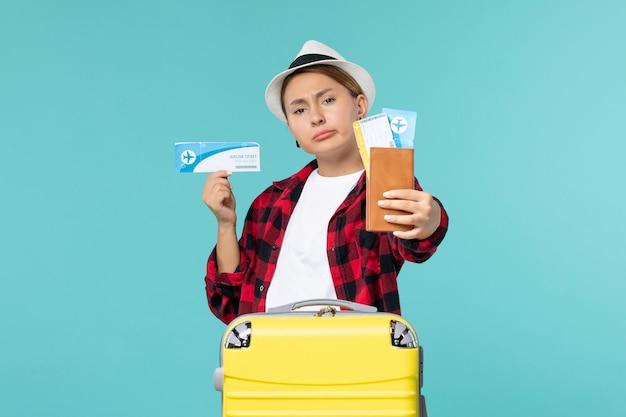Mulher jovem segurando a carteira e o ingresso de frente no espaço azul