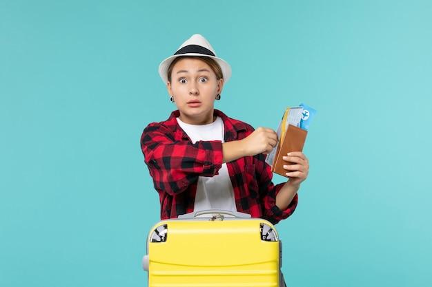 Mulher jovem segurando a carteira e os ingressos de frente no espaço azul claro