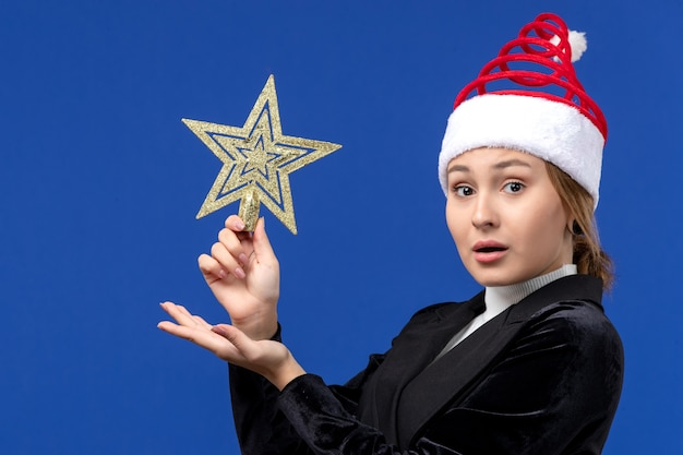 Mulher jovem segurando a decoração em forma de estrela de frente na parede azul, mulher, feriado