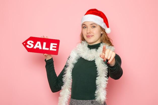 Mulher jovem segurando a escrita vermelha de venda na parede rosa foto de natal de ano novo.