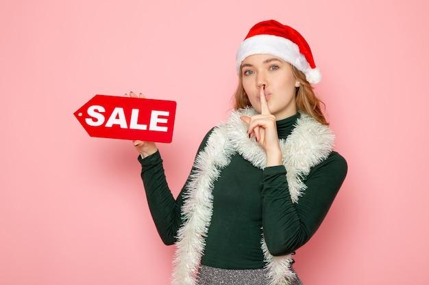 Mulher jovem segurando a escrita vermelha de venda na parede rosa natal, feriado de ano novo, foto, emoção de compra