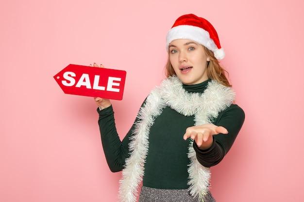 Mulher jovem segurando a escrita vermelha na parede rosa natal, feriado, ano novo, compras, moda, vista frontal