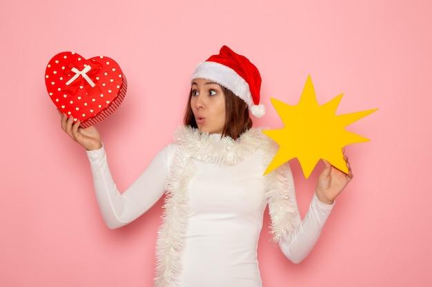 Mulher jovem segurando a figura amarela de frente e presente na parede rosa neve cor de natal feriados moda ano novo