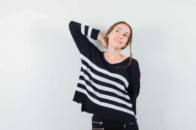 Mulher jovem segurando a mão atrás do pescoço, em malha listrada e calça preta, parecendo feliz