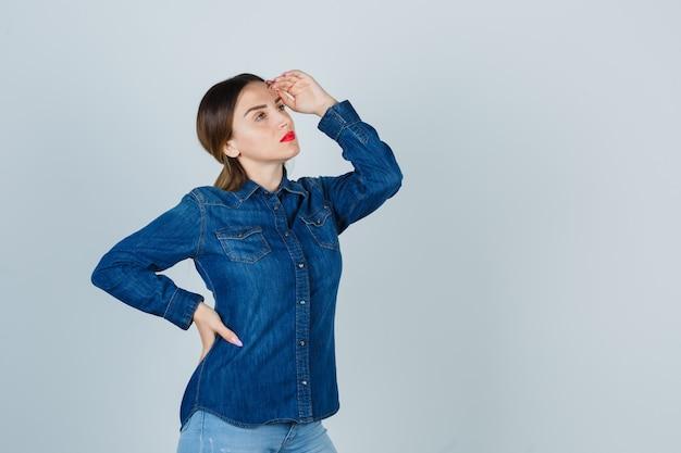 Mulher jovem segurando a mão na cabeça enquanto olha para longe, com uma camisa jeans e jeans e parecendo pensativa