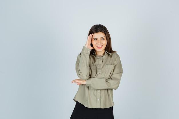 Mulher jovem segurando a mão na lateral do rosto na camisa, saia e parecendo feliz