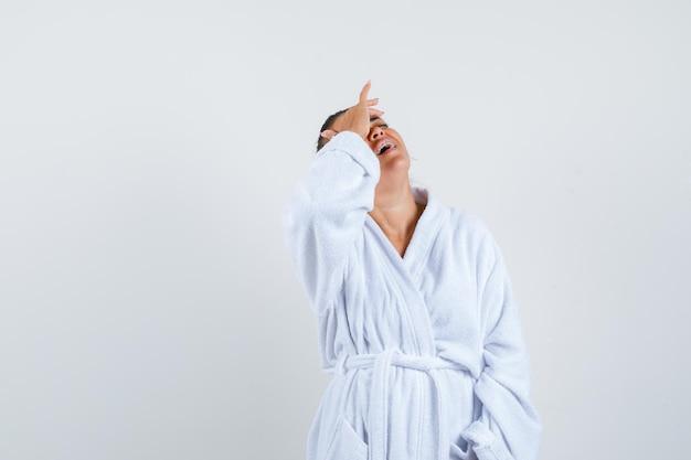 Mulher jovem segurando a mão na testa com um roupão de banho e parecendo esquecida