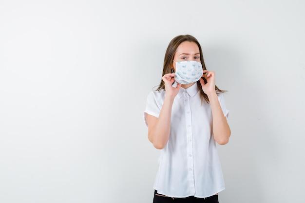 Mulher jovem segurando a máscara médica de mãos dadas