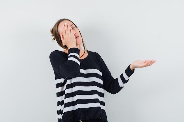 Mulher jovem segurando algo imaginário e cobrindo os olhos com uma das mãos em uma malha listrada e calça preta, parecendo preocupada