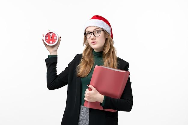 Mulher jovem segurando arquivos e relógio na parede branca do livro de natal de ano novo