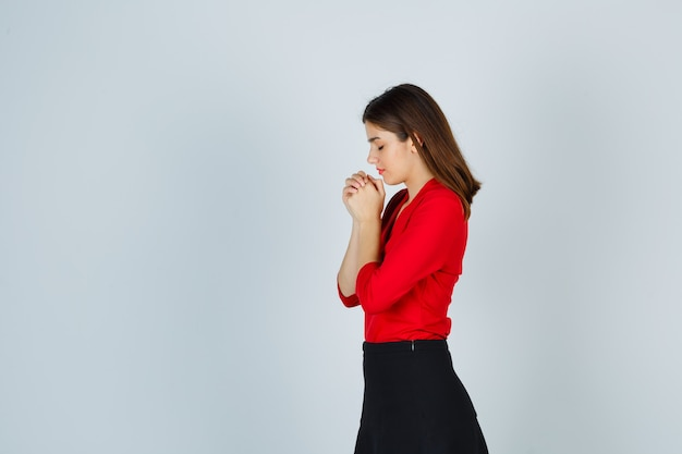 Mulher jovem segurando as mãos em posição de oração com uma blusa vermelha