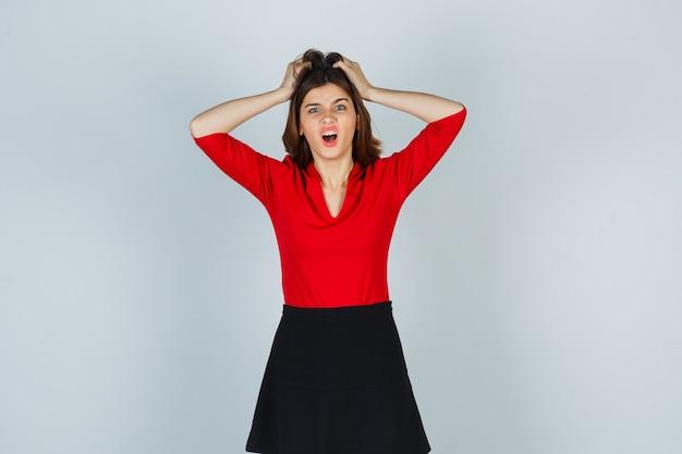 Mulher jovem segurando as mãos na cabeça com uma blusa vermelha, saia preta e parecendo irritada