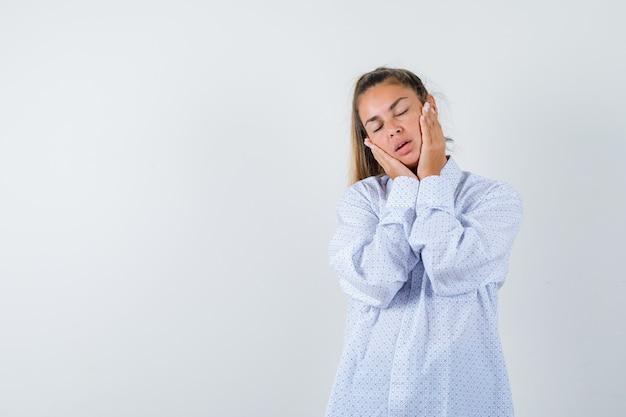 Mulher jovem segurando as mãos no rosto com uma camisa branca e parecendo cansada