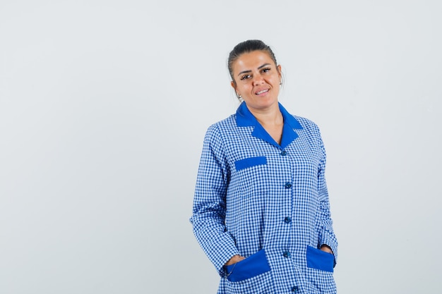 Mulher jovem, segurando as mãos nos bolsos, na camisa de pijama riscada azul e está linda. vista frontal.