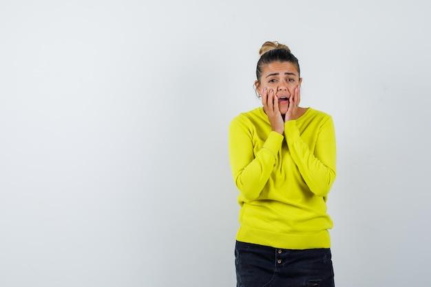Mulher jovem segurando as mãos perto da boca com um suéter amarelo e calça preta e parecendo surpresa